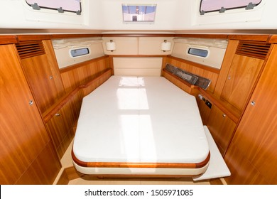 Sailing yacht interior. Double cabin on a charter yacht. Bareboat yacht interior - wood trim, light mattress and bedding, plenty of light from portholes. Comfortable berth for cruise on seas, oceans