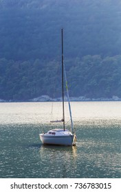 Sailing yacht on beautiful lake amidst wooded mountains