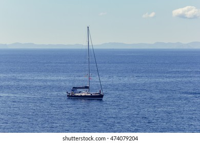 Sailing yacht on the Mediterranean Sea, calm water and blue mar, coast of the island Cabrera on background, captured from above.