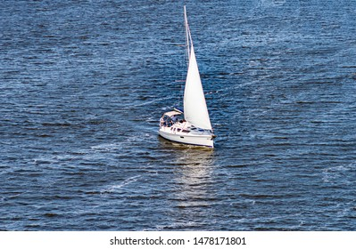 Sailing yacht sailing with an open white sail. Sports and recreation.