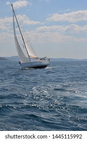 Sailing yacht race in Adriatic sea. Abandoned boat is sailing through the waves in strong wind. Yachting theme. Luxury sail boat.