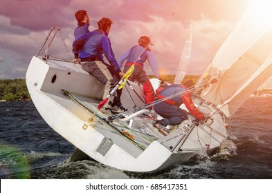 Sailing yacht race, regatta. Sail boat. Team athletes participating in the sailing competition. Recreational Water Sports. Extreme Sport Action. Healthy Active Lifestyle. Summer Fun Adventure