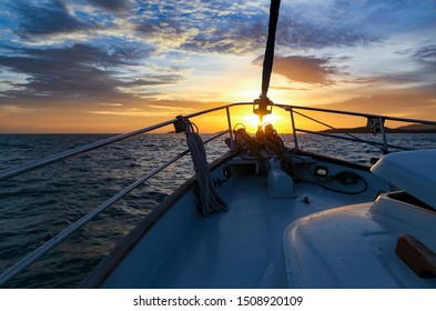 Sailing yacht standing at night on the mooring in the Andaman Sea of Indian Ocean. Modern luxury yacht at sunset against the night sky. Tropical sea and yacht with a white deck and mast in Thailand