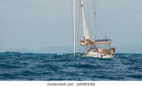 Sailing yacht in a storm at sea. White expensive yacht in a stormy ocean. Waves sweep across the deck. Sailboat goes under a sail with reef points. Hull is almost under the water