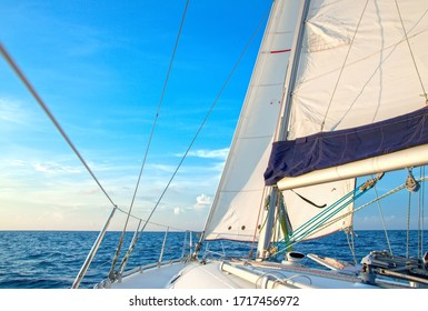Sailing yacht at sunset in the sea goes under full sails. White deck of a luxury charter yacht, rigging, mast, main sail, spinnaker and jib. Bareboat sailboat in the ocean. Yacht in strong wind