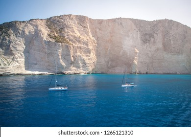 Sailing yachts are in the bay near the cliff.