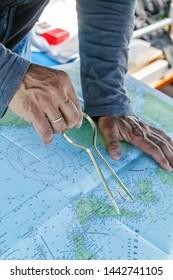 Sailor with divider in front of navigation chart of coastal area. Captain navigating sail boat ship