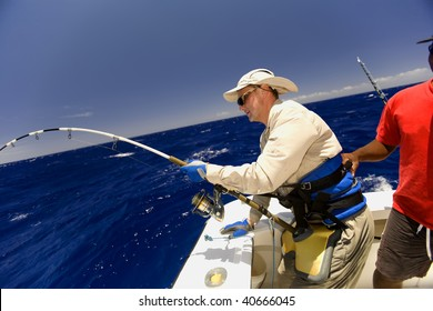 The sailor helps the diligent fisher to take out huge fish