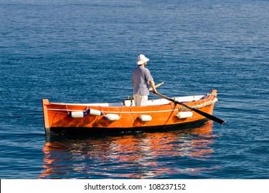 Sailor rowing on wooden taxi boat in Zadar, Croatia