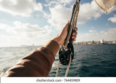 Sailor or tourist in windproof brown leather jacket holds on to rope or cord inside pulley, in nautical knot on a sailing boat or yacht, during cruise or race competition in open sea