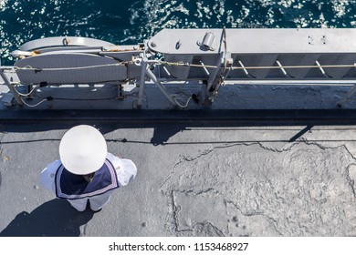 sailor in white uniform standing peacefully on the deck of a warship. A military warship and military sailor on deck.