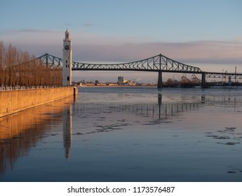 The Sailors' Clock Tower on Quai de l'Horloge with the Jacques Cartier Bridge in the distance in Montreal.