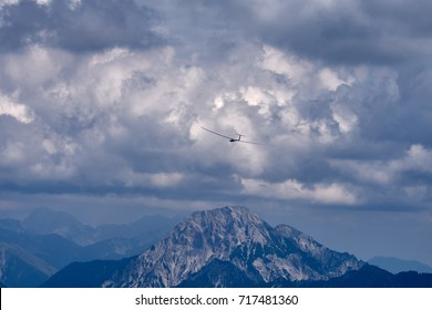 Sailplane gliding over a mountain top in the mountains of Dobratsch Nature Park in the Austrian Alps