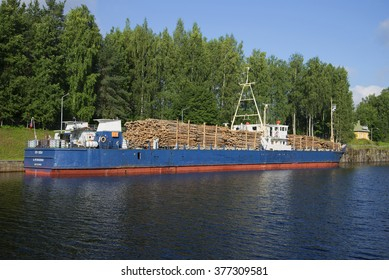 "THE SAIMAA CANAL, FINLAND - AUGUST 09, 2015: Russian ship ""STK-1004"" loaded with timber stands in the customs area of the Saimaa canal"