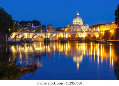 Saint Angel bridge or Roman bridge Ponte Sant Angelo, once the Aelian Bridge or Pons Aelius and St. Peter's cathedral with a mirror reflection in Tiber River during morning blue hour in Rome, Italy.