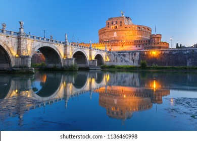 Saint Angel castle and bridge with mirror reflection in Tiber River during morning blue hour in Rome, Italy.