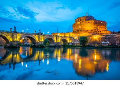 Saint Angelo castle and bridge with mirror reflection in Tiber River during evening blue hour in Rome, Italy.