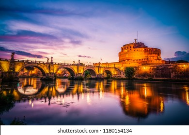 Saint Angelo castle and bridge with mirror reflection in Tiber River at sunset in Rome, Italy