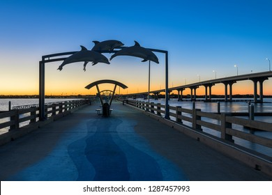 SAINT AUGUSTINE, FLORIDA, USA - DECEMBER 5, 2018: Silhouette of dolphin sculpture above the Vilano Beach Fishing Pier  at sunset