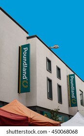 SAINT AUSTELL, CORNWALL, UK - JULY 9, 2016: Poundland store sign on white wall with blue sky. Saint Austell high street shop. Architectural detail. Bargain budget business trader.