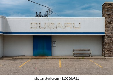 SAINT CLOUD, UNITED STATES - May 30 2018: A closed Subaru dealership sits vacant. The stained outline of the Subaru logo is visible on the building.