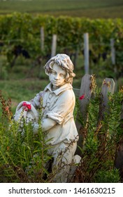 Saint Emilion, France - September 12, 2018: Statue of a boy holding a basket with grapes on the background of vineyards in the Saint Emilion region. France
