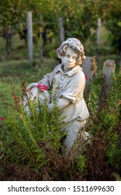 Saint Emilion, France - September 12, 2018:Statue of a boy holding a basket with grapes on the background of vineyards in the Saint Emilion region. France