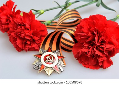 Saint George ribbon with order of the Great Patriotic and red carnations on gray