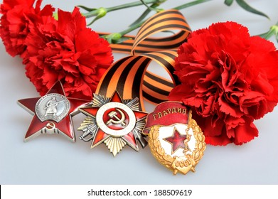 Saint George ribbon with orders of the Great Patriotic and red carnations on gray