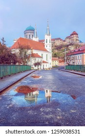 Saint Ignatius church and monumental basilica with reflection in rain water, Esztergom, Hungary. Travel destination. Cultural heritage. Religious architecture. Purple photo filter.