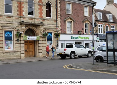 SAINT IVES, CAMBRIDGESHIRE, UK - CIRCA MAY 2016: Busy British market town centre with people seen walking past a pharmacy store, with parked cars in view.