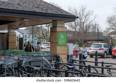 SAINT IVES, CAMBRIDGESHIRE, UK - CIRCA MARCH 2017: Entrance area to a well known British supermarket chain, showing a nearby bike rack and a disabled parking sign near to the entrance.