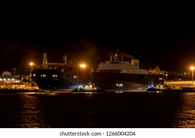 """Saint John, NB, Canada - December 22, 2018: The Saudi ship """"Bahri Yanbu"""" arrives in Saint John to pick up a shipment of LAVs as part of a controversial arms deal. Tugs help the ship dock."""