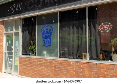 "Saint John, NB, Canada - July 20, 2019: King Canna is an unlicensed cannabis dispensary. There is a neon ""OPEN"" sign in the window. Unlicensed cannabis stores are common in Canada."