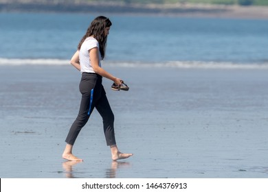 Saint John, NB, Canada - July 20, 2019: A woman walks barefoot across a wet public beach at low tide on a sunny day. She is dressed in a white tee shirt and black pants, and is carrying her sandals.