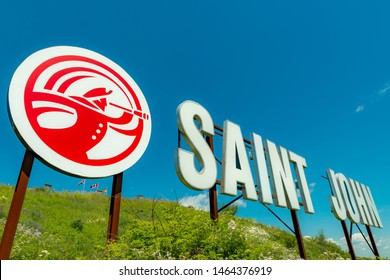 "Saint John, NB, Canada - July 20, 2019: The ""Saint John"" sign overlooks the harbor from Fort Howe. The cities ""Loyalist"" logo is to the left of the sign. The sign was installed in 1999."