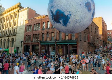 Saint John, NB, Canada - July 20, 2019: An inflatable moon over a crowd of people at the annual Moonlight Bazaar. The event attracts thousands of visitors, and features assorted vendors and music.