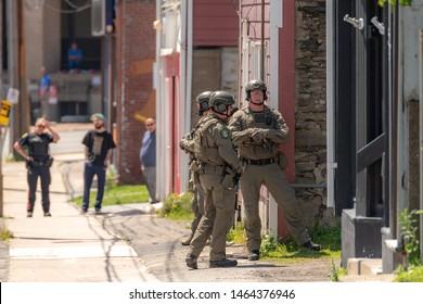 Saint John, NB, Canada - July 24, 2019: Police officers prepare to raid a building. They are heavily armed and are wearing tactical gear. Another officer and bystanders watch from the distance.