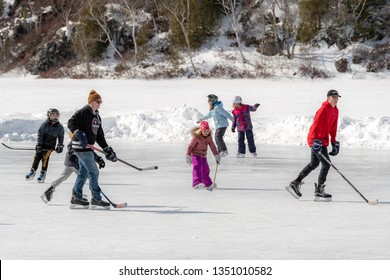 Saint John, NB, Canada - March 9, 2019: Adults and children practice outdoor ice hockey on a frozen lake.