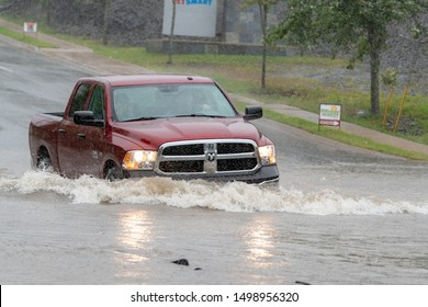 Saint John, NB, Canada - September 7, 2019: A truck drives through water on a flooded road. The flood was caused by wind and rain from Hurricane Dorian. Rain visible in the air (it is not noise).