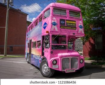 Saint John, New Brunswick—June 20, 2018; pink double decker tour bus turns on sharp corner in historic brick district of Saint John's canada.