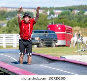 Saint John, New Brunswick, Canada - September 4, 2015: An acrobat performs at the Saint John Exhibition. He is bouncing on a long trampolene.