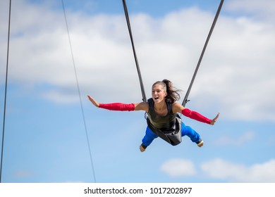 Saint John, New Brunswick, Canada - September 4, 2015: An acrobat performs at the Saint John Exhibition. She is held high up by cords attached to her waist.