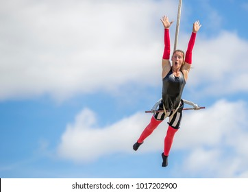 Saint John, New Brunswick, Canada - September 4, 2015: An acrobat performs at the Saint John Exhibition. She is high up on a trapeze.