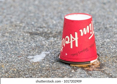 Saint John, New Brunswick, Canada - January 16, 2018: A discarded Tim Hortons coffe cup rests upside down in a parking lot.