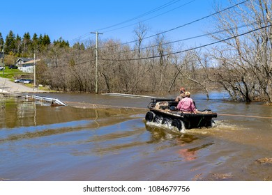 Saint John, New Brunswick, Canada - May 5, 2018: A volunteer ferries a lady across a flooded road in a small all terrain vehicle.
