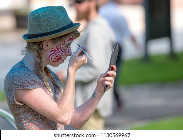 Saint John, New Brunswick, Canada - July 1, 2018: A face painter paints her own face in preparation for Canada Day celebrations. She uses a mirror to help.