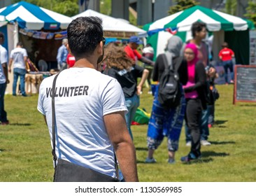Saint John, New Brunswick, Canada - June 16, 2018: A man volunteering at an the Saint John International Culture Fest. His tee shirt says VOLUNTEER across the back. People and tents in background.