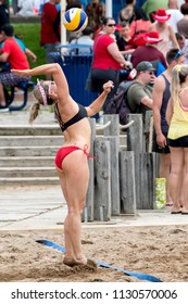Saint John, New Brunswick, Canada - July 1, 2018: Beach vollyball by Market Square. A woman serves the vollyball.