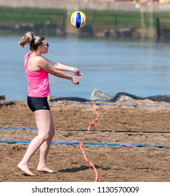 Saint John, New Brunswick, Canada - July 1, 2018: Beach vollyball by Market Square. A woman hits a vollyball into the air.